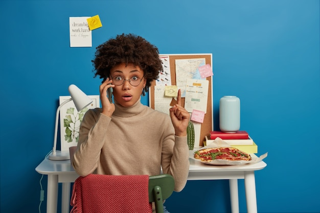Photo of surprised shocked female worker in glasses points up during phone conversation, calls someone via smartphone, sits at chair against desktop with pizza, board with notes, desk lamp, blue wall