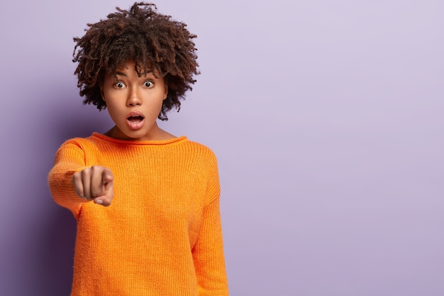 Photo of surprised startled emotional curly woman points fore finger straight , opens mouth from shock, demonstrates something in front, wears casual clothes, models over purple wall