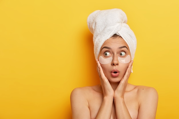 Photo of surprised young afro woman touches cheeks with hands, looks aside with stupor, wears wrapped towel, applies white patches under eyes, models over yellow background, has spa procedure