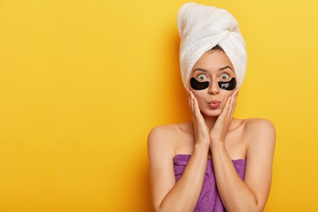 Photo of surprised young female model touches cheeks, keeps lips rounded, applies black undereye patches, reduces surface skin, wears wrapped towel