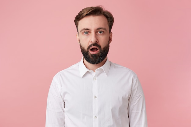 Photo of surprised young handsome bearded man who was told the secret, wearing a white shirt. looking at the camera with wide open mouth isolated over pink background.