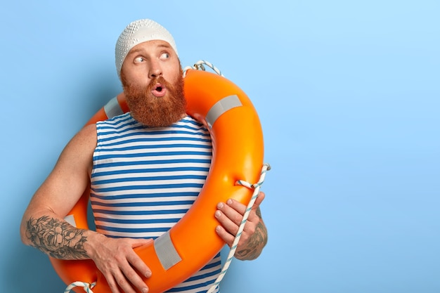 Photo of surprised young man wonders something, wears white rubber swimcap, striped vest, carries lifebuoy, shocked hear instruction from coach