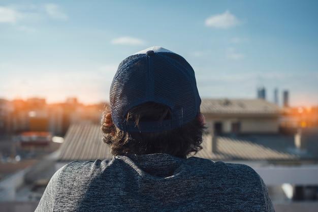 長い髪の帽子をかぶった少年の後ろから撮った写真。ビルの屋上から街を眺める