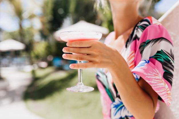 Foto della mano femminile abbronzata che tiene un bicchiere di bevanda fredda alla frutta.