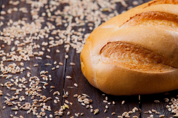 Photo of tasty fresh bread loaf on the wonderful brown wooden background