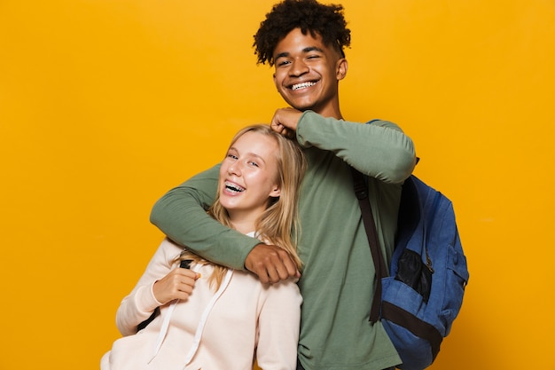 Photo of teen people man and woman 16-18 wearing backpacks laughing and hugging together, isolated over yellow background