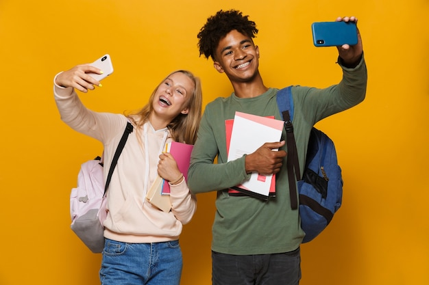 Photo of teen students man and woman 16-18 wearing backpacks taking selfie on mobile phones and holding exercise books, isolated over yellow background