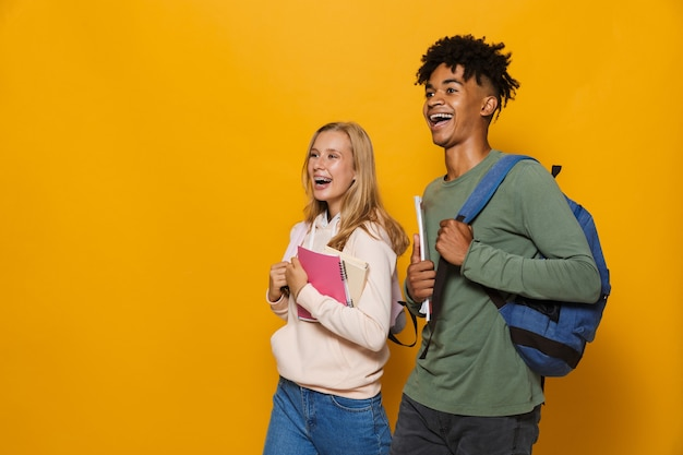 Photo of teenage people guy and girl 16-18 wearing backpacks smiling and holding exercise books while walking, isolated over yellow background