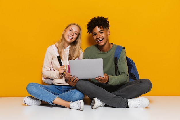 Photo of teenage students man and woman 16-18 using silver laptop while sitting on floor with legs crossed, isolated over yellow background
