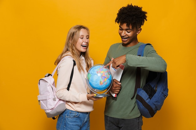 Photo of teenage students man and woman 16-18 wearing backpacks holding earth globe and exercise books, isolated over yellow background