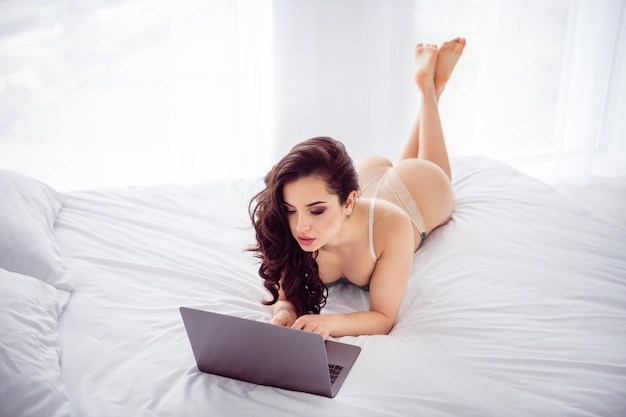 Photo of tempting home remote worker lady quarantine online laptop chat ready undress on screen fit body for money write read vip customer message wear bikini lying linen bedroom indoors