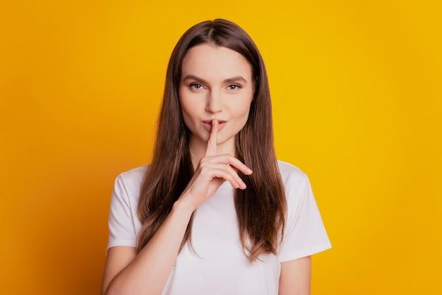 Photo of tender flirty lady finger close lips wear white t-shirt posing on yellow background Premium Photo