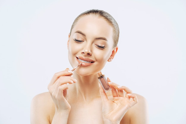 Photo of tender woman with perfect makeup, applies lip gloss, uses lip concealer brush, has dark combed hair, stands bare shoulders indoor, cares about herself, isolated on white wall.