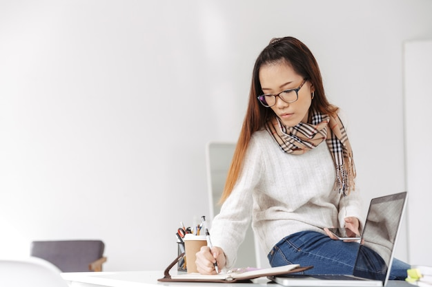 Photo of thinking asian female worker wearing glasses using cellphone and writing on her diary while sitting at table in office