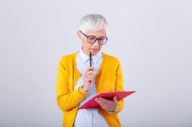 Photo of a thinking mature business woman isolated over grey wall holding clipboard and pen. image of confused senior woman looking at documents