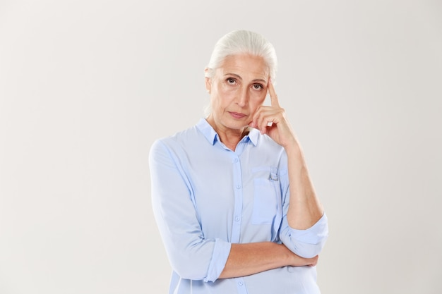 Photo of thinking old lady in blue shirt