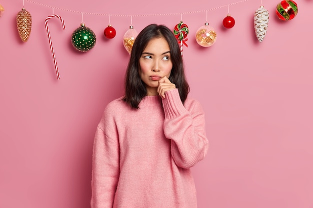 Photo of thoughtful brunette asian woman stands displeased dressed in casual jumper keeps hand on face thinks about decoration of house before new year poses