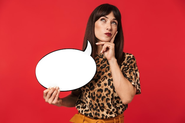 Photo of thoughtful brunette woman 30s dressed in stylish outfit looking upward and holding blank speech bubble isolated over red wall