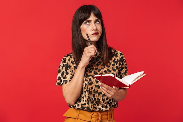 Photo of thoughtful brunette woman 30s dressed in stylish outfit looking upward and writing notes in planner book isolated over red wall