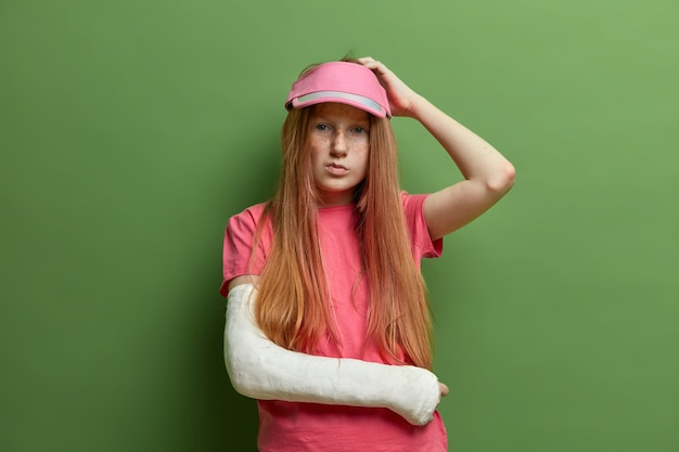 La foto di una donna premurosa e indecisa si gratta la testa e cerca di ricordare tutti i dettagli sull'incidente avvenuto con lei, ha un braccio rotto nel gesso, vestita casualmente, isolata sul muro verde