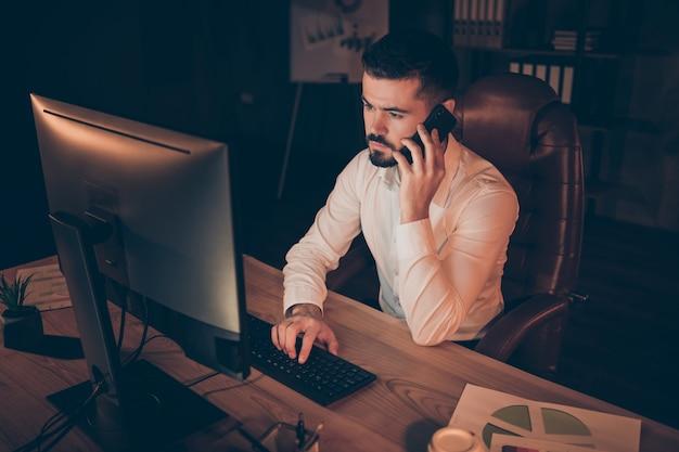 Photo of thoughtful man communicating phone typing pc