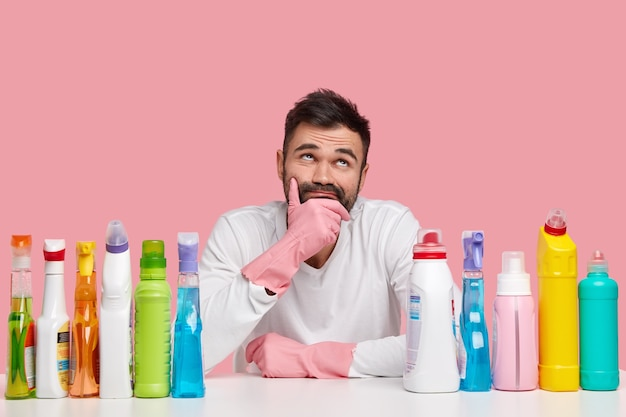 Photo of thoughtful man holds chin, looks pensively upwards, wears white jumper and gloves, uses washing up liquid, cleanser, isolated over pink space