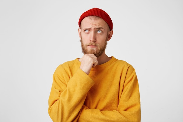 Photo of thoughtful man isolated over white wall wall