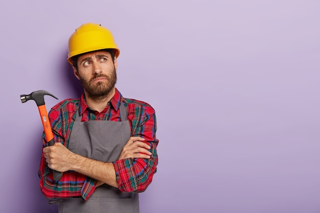 Photo of thoughtful tired mannual worker holds hammer, keeps arms crossed over chest, thinks about what to repair