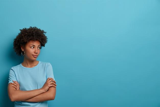 La foto di una donna premurosa ha una pelle sana, tiene le mani incrociate sul petto, concentrata da parte, indossa una maglietta casual, isolata sul muro blu, uno spazio vuoto per le tue informazioni, fa dei piani