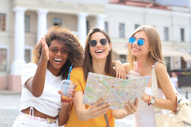 Photo of three girls enjoying sightseeing outdoor. beautiful female tourists exploring city with map.