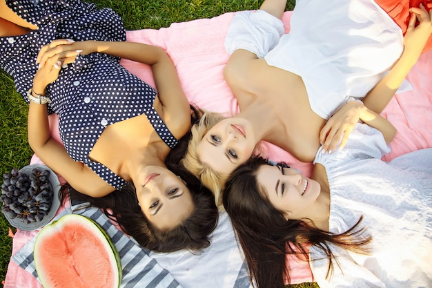 Photo of three happy girls lying on green grass and smiling.