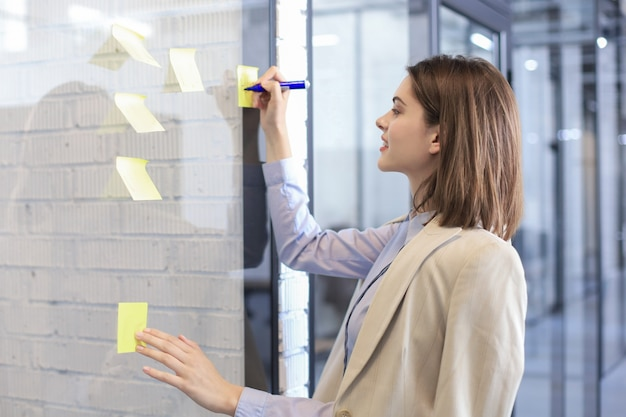 Фото через стекло привлекательной деловой женщины размещают наклейки на стекле в офисе и пишут на них.
