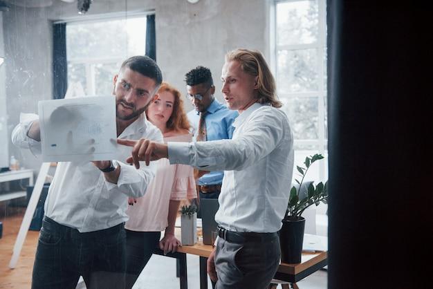 Фото сквозь стекло. молодая многорасовая команда в официальной одежде в офисе, глядя на прайс-лист