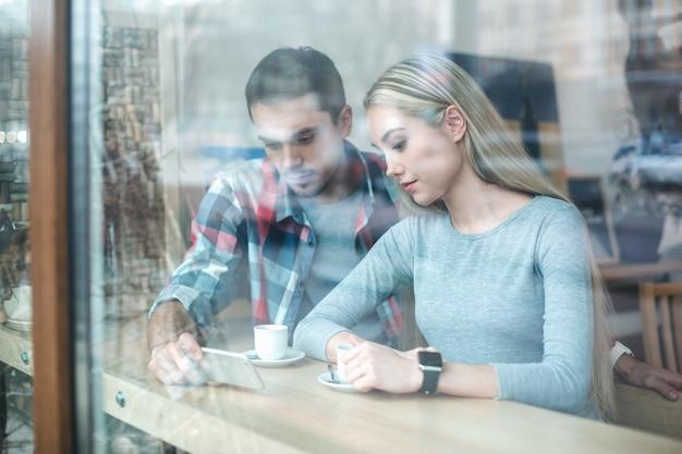 窓越しの写真。カフェでデート。スタイリッシュなインテリアのカフェで若いカップル。おいしいコーヒーを飲む学生。彼らは携帯電話を使っています