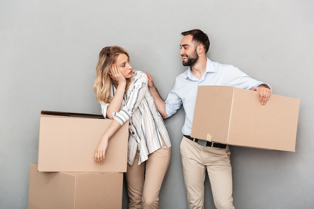 Photo of tired european couple in casual clothing looking at each other and carrying cardboard boxes isolated