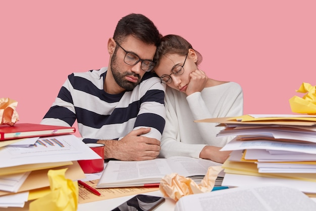 Photo of tired overworked sleepy young woman and man keep heads near, look fatigue, wear optical spectacles, read information from encyclopedia
