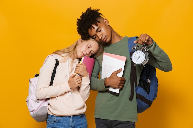 Photo of tired students man and woman 16-18 wearing backpacks sleeping while holding exercise books and alarm clock, isolated over yellow background