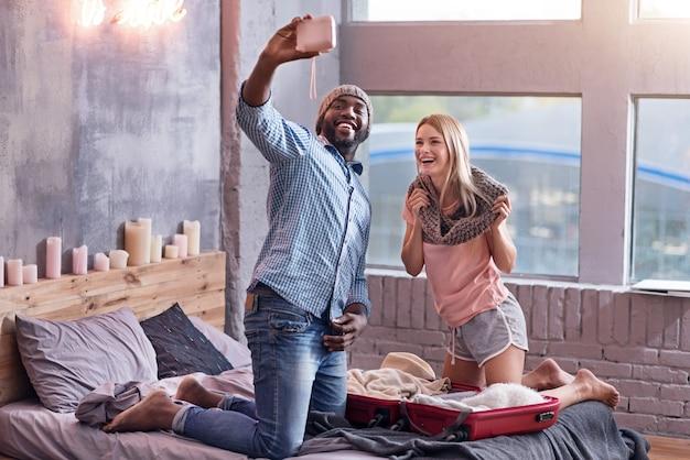 覚えておくべき写真。ベッドで一緒に自分撮りをし、楽しみながら帽子とスカーフを身に着けている幸せな国際的な若いカップル。