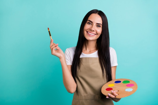 Photo of toothy cheerful beaming cute nice pretty woman looking at you holding colorful palette with brush with hands isolated vivid teal color background
