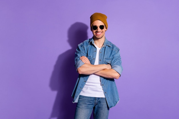 Photo of toothy smiling cheerful cool guy with hands folded showing his beaming teeth isolated over purple vivid color background