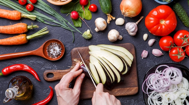 Photo on top of fresh vegetables, champignons, cutting board, oil, knife, eggplant, chef's hands