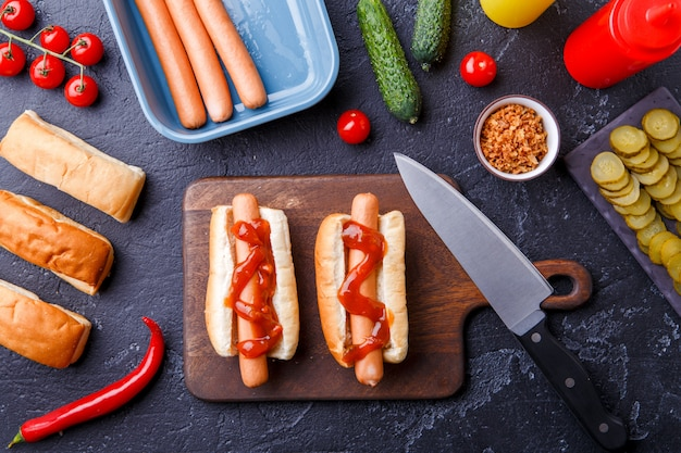Photo on top of two hotdogs on cutting board on table with sausages