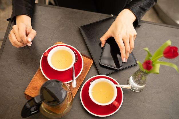 カップ、ティーポット、スマートフォン、日記と木製の背景に女性の手の写真上面図。コーヒーブレイク