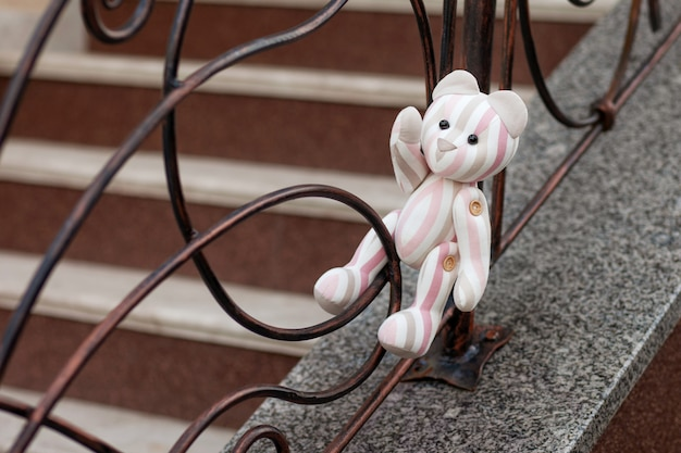 Photo of toy bear. vintage teddy bear of linen fabric. a lonely toy bear sitting on  forged lattice