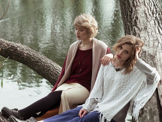 Photo of a two beautiful women posing on a tree near lake.