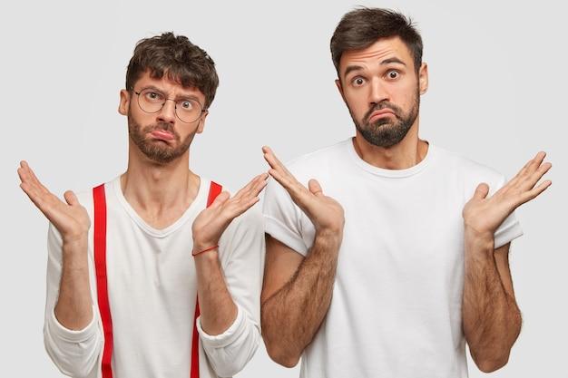 Foto di due uomini barbuti spensierati e spensierati che scrollano le spalle, hanno un'espressione facciale esitante, nessuna idea, sguardo interrogato, sentirsi incerti, stare spalla a spalla contro il muro bianco