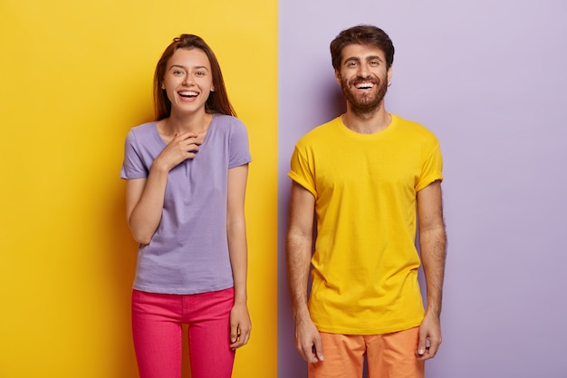 Photo of two delighted young woman and man stand together, express good emotions, smile happily