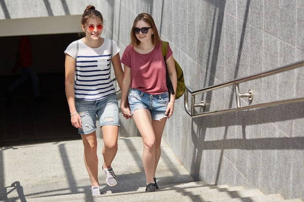 Photo of two female lesbians hold hands, have walk in city, stand near subway, wears casual t shirts and jean shorts, have happy expressions, enjoy sunny day. people and relationship concept