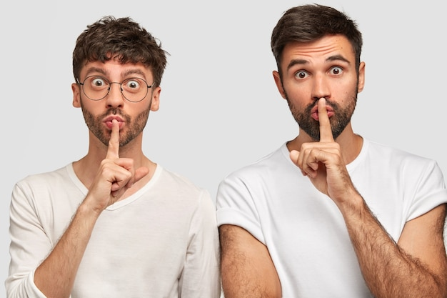 Photo of two friendly companions make silence sign, keep fore fingers on lips, looks surprisingly, tell secret information, isolated over white wall. men show shush gesture.