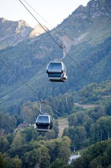 Photo of two funiculars among mountain hills among vegetation